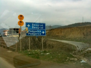Dual language road sign for Belgrade and Podgorica. Note also the yellow circle road signs for lorries and tanks. Mitrovica, Kosovo.